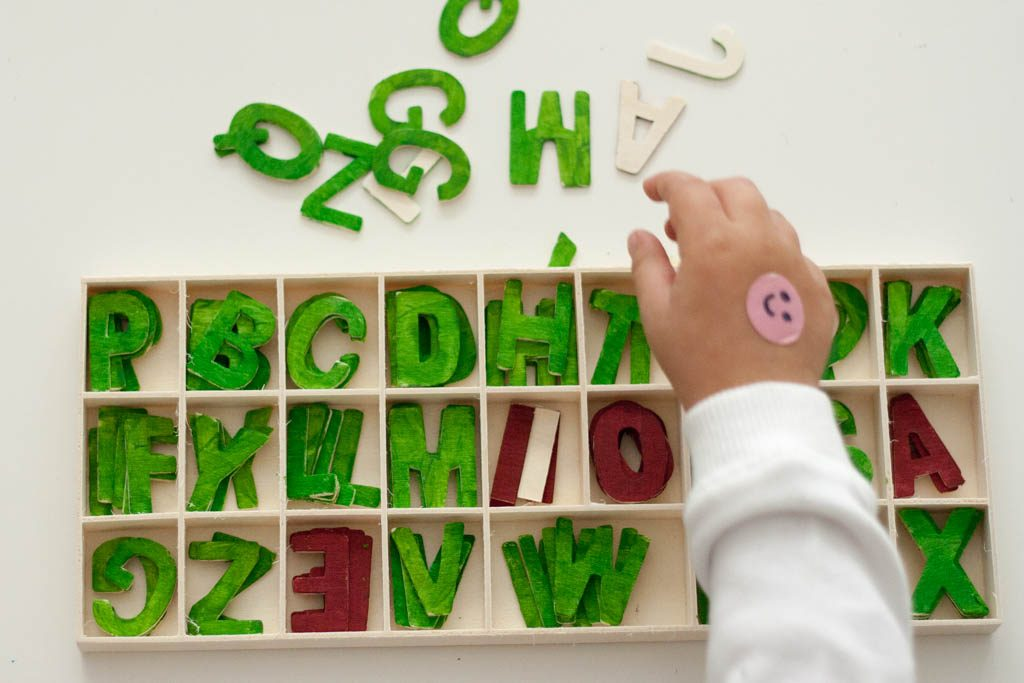 niña jugando con abecedario montessori