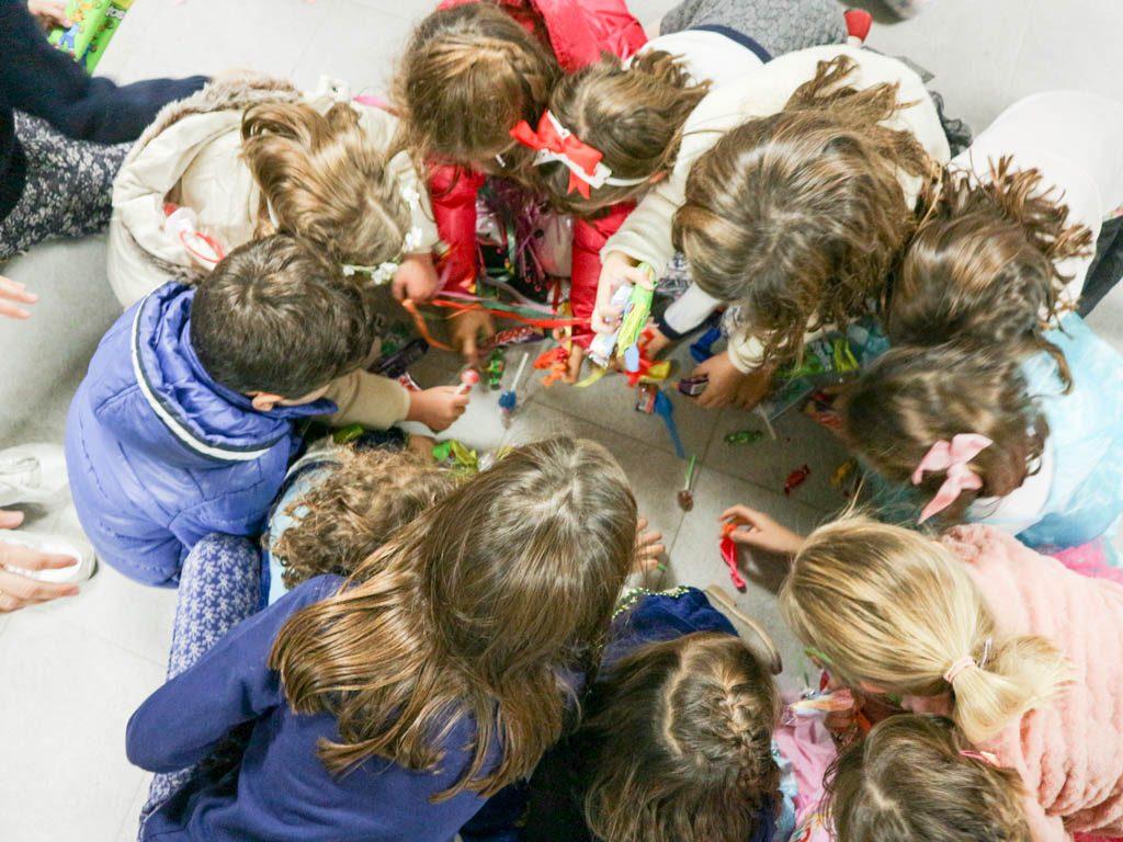 niños recogiendo sorpresas de una piñata