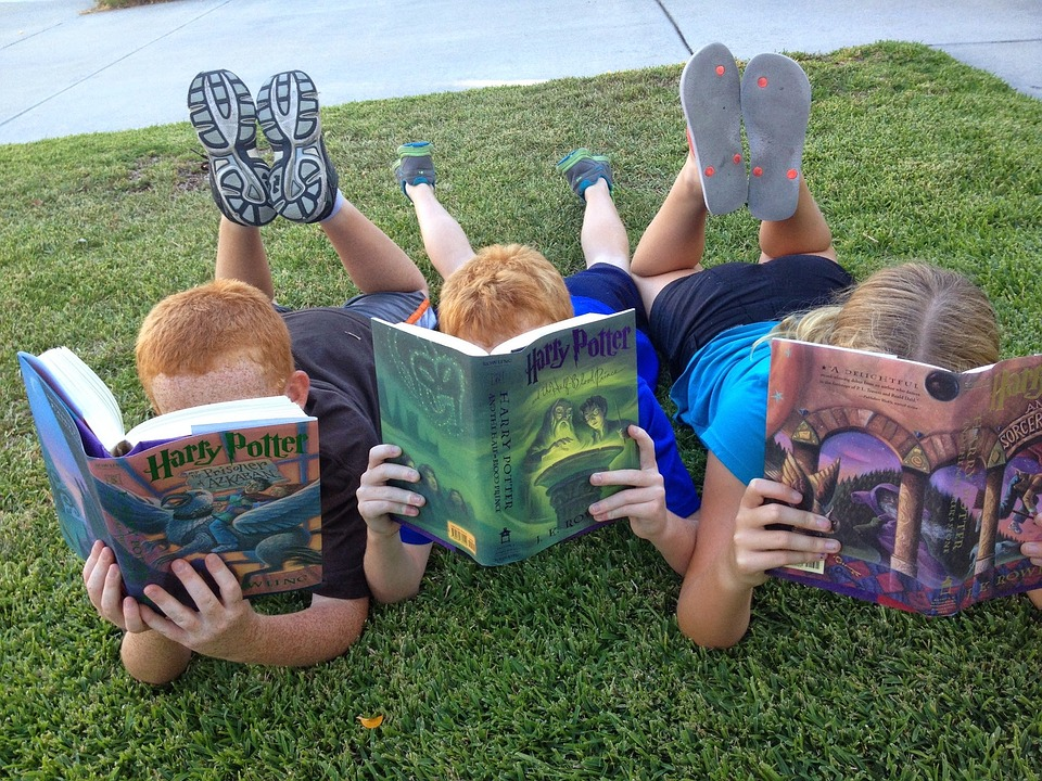 tres niños leyendo harry potter